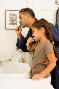 father and daughter brushing teeth with tips from their dentist in hickory flats