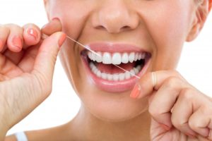 woman smiling flossing her teeth