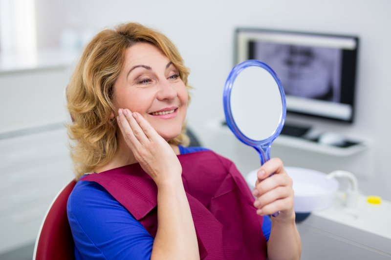 a woman looking at her smile in the mirror at the dentist's office