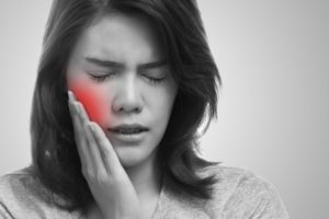 pained woman with toothache puts her hand to her cheek