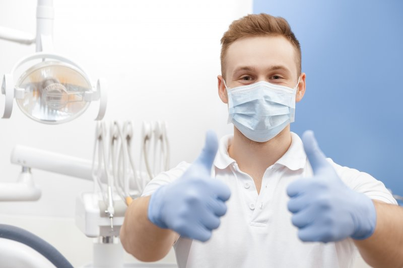 Dentist gives thumbs-up with gloves