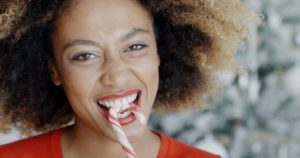 woman biting into candy cane